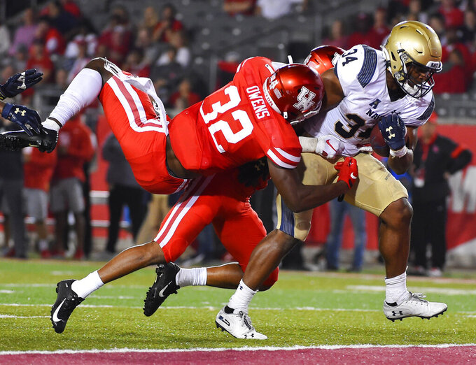 Navy fullback Jamale Carothers, right, breaks the tackles of Houston safety Gervarrius Owens (32) and cornerback Damarion Williams en route to a touchdown during the second half of an NCAA college football game, Saturday, Nov. 30, 2019, in Houston. (AP Photo/Eric Christian Smith)