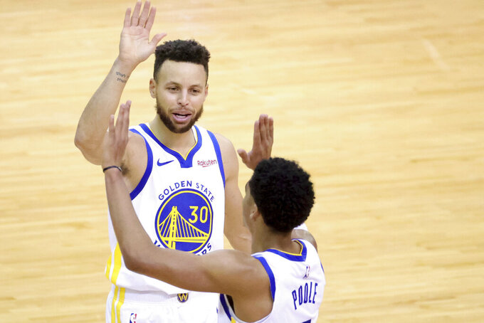 Golden State Warriors' Stephen Curry, rear, high-fives Jordan Poole during the second quarter against the Houston Rockets in an NBA basketball game Wednesday, March 17, 2021, in Houston. (Carmen Mandato/Pool Photo via AP)