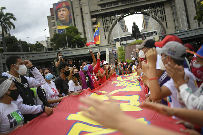 "People shout as they hold a sign with a message that reads in Spanish: ""Stay strong Colombia"", on Bolivar Avenue in Caracas, Venezuela, Saturday, May 8, 2021, during a gathering of Venezuela government supporters to show solidarity with the protesters in Colombia who were against a proposed tax plan, since withdrawn by the president. (AP Photo/Matias Delacroix)"