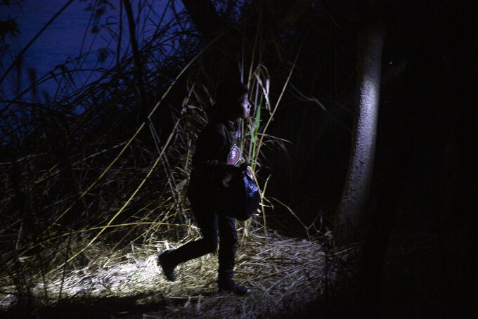 FILE - In this Wednesday, March 24, 2021, file photo, young child walks alone through the brush after being smuggled across the Rio Grande river in Roma, Texas. The government failed to prepare for a big increase in children traveling alone as President Joe Biden ended some of his predecessor's hardline immigration policies and decided he wouldn't quickly expel unaccompanied kids from the country like the Trump administration did for eight months. (AP Photo/Dario Lopez-Mills, File)