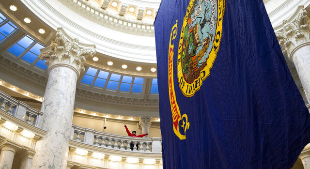 A young visitor to the Idaho Statehouse celebrates the giant state flag hanging in the rotunda as the Idaho Legislature convened Monday, Jan. 11, 2021 in Boise. (Darin Oswald/Idaho Statesman via AP)