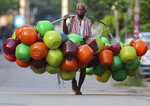 An Indian man wearing a face mask as a precaution against the coronavirus walks with plastic pots for sale on a street in Hyderabad, India, Saturday, Aug. 1, 2020. India is the third hardest-hit country by the pandemic in the world after the United States and Brazil. (AP Photo/Mahesh Kumar A.)(AP Photo/Mahesh Kumar A.)