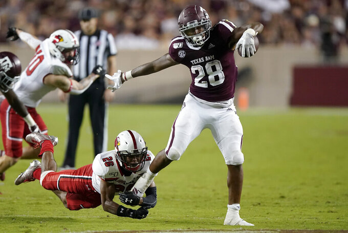 Texas A&M running back Isaiah Spiller (28) shakes off a tackle by Lamar defensive back Tariq Gordon (26) during a touchdown run in the second half of an NCAA college football game, Saturday, Sept. 14, 2019, in College Station, Texas. (AP Photo/Sam Craft)