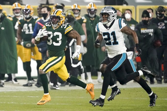 Green Bay Packers' Aaron Jones runs past Carolina Panthers' Jeremy Chinn during the first half of an NFL football game Saturday, Dec. 19, 2020, in Green Bay, Wis. (AP Photo/Morry Gash)