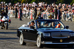 Japanese Emperor Naruhito, center, and Empress Masako, right, wave during the royal motorcade in Tokyo, Sunday, Nov. 10, 2019. (AP Photo/Eugene Hoshiko)