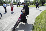 A police officer, center right, detains a protester dressed as a Russian police officer before a court hearing of the New Greatness group who are charged with the organization of an extremist association in Moscow, Russia, Thursday, Aug. 6, 2020. Arrests of the two youngest members of the New Greatness group - 17-year-old Anna Pavlikova and 19-year-old Maria Dubovik - prompted a mass protest in August 2018, after which the two teenagers were released under house arrest. (AP Photo/Pavel Golovkin)