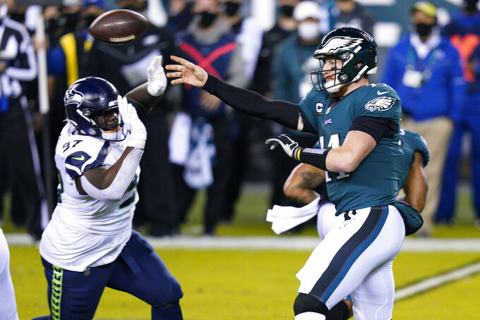 Philadelphia Eagles' Carson Wentz (11) passes against Seattle Seahawks' Poona Ford (97) during the first half of an NFL football game, Monday, Nov. 30, 2020, in Philadelphia. (AP Photo/Chris Szagola)