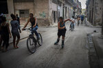 In this Nov. 9, 2019 photo, a youth rollerblades amid cyclists and pedestrians in Old Havana, Cuba. The city will celebrate its 500th anniversary on Nov. 16. (AP Photo/Ramon Espinosa)