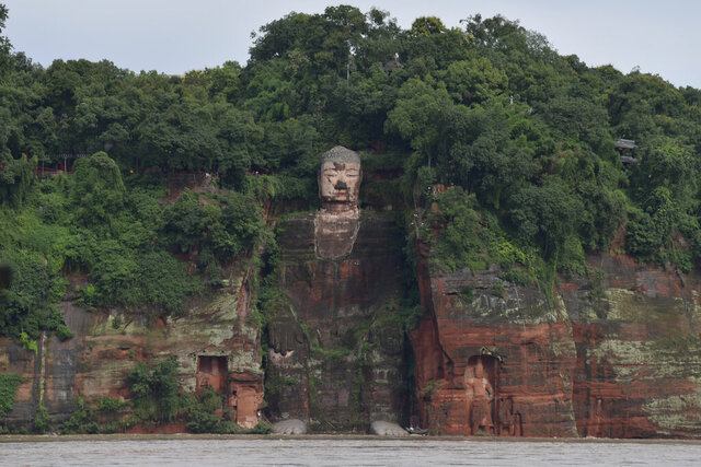 In this photo released by China's Xinhua News Agency, floodwaters flow near the historic Giant Buddha in Leshan in southwestern China's Sichuan Province on Aug. 18, 2020. China faced a double whammy Wednesday of flooding and landslides from unusually heavy seasonal rains and a typhoon that came ashore on its southern coast. (Xu Bingjie/Xinhua via AP)