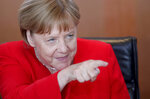German Chancellor Angela Merkel points as she arrives for the weekly cabinet meeting at the Chancellery in Berlin, Germany, Wednesday, June 19, 2019. (AP Photo/Michael Sohn)