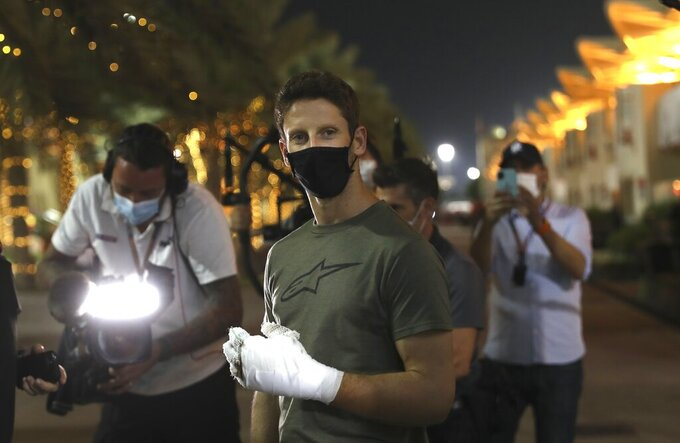 Haas driver Romain Grosjean of France arrives to paddock to thank the marshals Thursday, Dec. 3, 2020, in Bahrain International Circuit in Sakhir, Bahrain.  Grosjean escaped with only minor burns when his Haas car exploded into a fireball after crashing on the first lap at last weekend's Bahrain GP. (AP Photo/Kamran Jebreili)