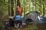 Cheryl Gamble and Clint Marable pose near the tent they a tent in the woods off Jefferson Road Tuesday,  July 13, 2021, in Athens, Ga. The couple have been without permanent housing on and off for the past several years, but are looking forward to the possibility of having a more stable living situation through a government-funded facility. (Kayla Renie/Athens Banner-Herald via AP)