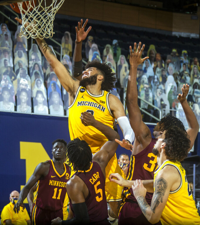 Michigan forward Isaiah Livers (2) makes a basket over Minnesota guard Marcus Carr (5) in the second half of an NCAA college basketball game at Crisler Center in Ann Arbor, Mich., Wednesday, Jan. 6, 2021. (AP Photo/Tony Ding)