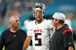 Atlanta Falcons quarterback AJ McCarron (5) is assisted off the field after he was injured on a play, during the first half of a preseason NFL football game against the Miami Dolphins, Saturday, Aug. 21, 2021, in Miami Gardens, Fla. (AP Photo/Lynne Sladky)