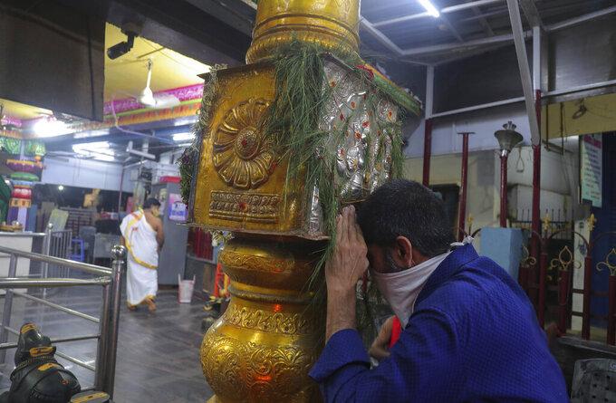 A man wearing a scarf as a precaution against the coronavirus offers prayers at Shakti Ganesh temple in Hyderabad, India, Tuesday, Sept. 22, 2020. (AP Photo/Mahesh Kumar A.)