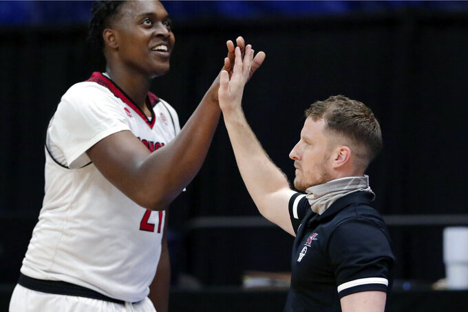 Nicholls State center Ryghe Lyons (21) high-fives coach Austin Claunch during the second half of the team's NCAA college basketball game against Northwestern State in the Southland Conference men's tournament semifinals Friday, March 12, 2021, in Katy, Texas. (AP Photo/Michael Wyke)