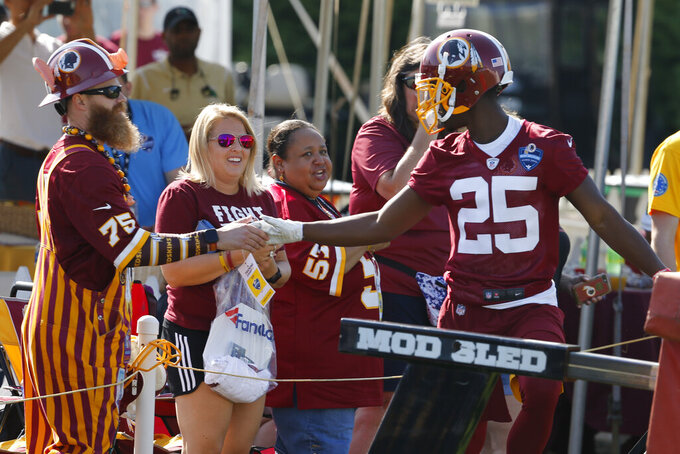 FILE - In this July 25, 2019, file photo, Washington Redskins cornerback Jimmy Moreland (25) greets fans as he heads to the practice field during the first day of NFL football training camp in Richmond, Va. He's one of the smallest players in camp with the Redskins, but cornerback Jimmy Moreland will arrive at the team's practice facility in Ashburn on Tuesday, Aug. 13, having had one of the biggest impacts on the team so far this preseason. (AP Photo/Steve Helber, File)