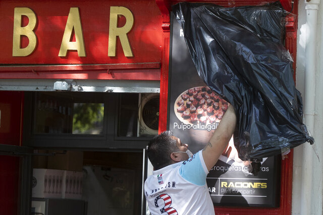 A worker uncovers the front of a bar ready to open for the first time in over two months in Madrid, Spain, Monday, May 25, 2020. Spain is making progress on its staggered plan out of the confinement against the coronavirus. Roughly half of the population, including residents in the biggest cities of Madrid and Barcelona, enters phase 1, Monday which allows for social gatherings in limited numbers, restaurant and bar services with outdoor sitting and some cultural and sports activities. (AP Photo/Paul White)