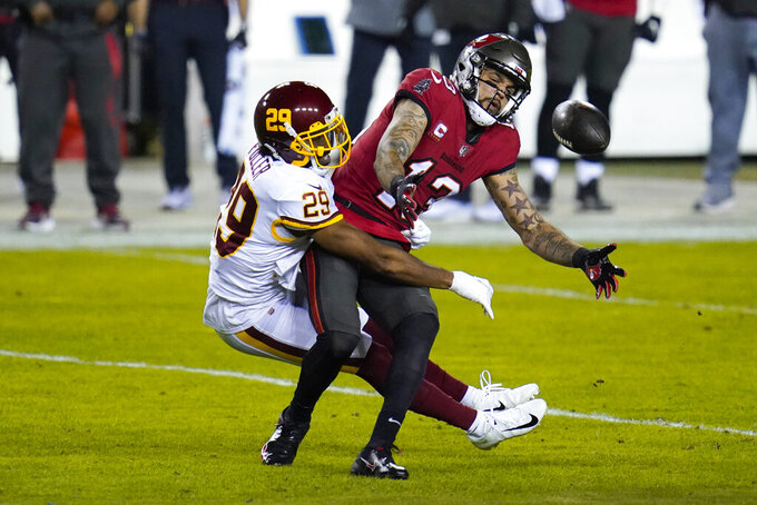 Washington Football Team cornerback Kendall Fuller (29) breaks up a pass intended for Tampa Bay Buccaneers wide receiver Mike Evans (13) during the first half of an NFL wild-card playoff football game, Saturday, Jan. 9, 2021, in Landover, Md. (AP Photo/Julio Cortez)