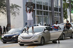 A protester of the death of George Floyd stands on his car as he and others demonstrate Sunday, May 31, 2020, in Miami. Floyd died May 25 after he was pinned at the neck by a Minneapolis police officer. (AP Photo/Wilfredo Lee)