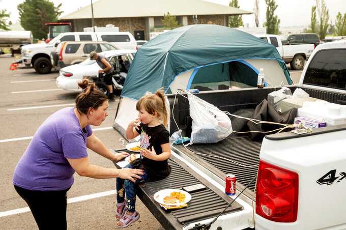 Jackie Armstrong, a Chester resident evacuated from the Dixie Fire, speaks with daughter Zoey Armstrong, 3, at a Susanville, Calif., evacuation shelter on Friday, Aug. 6, 2021. (AP Photo/Noah Berger)