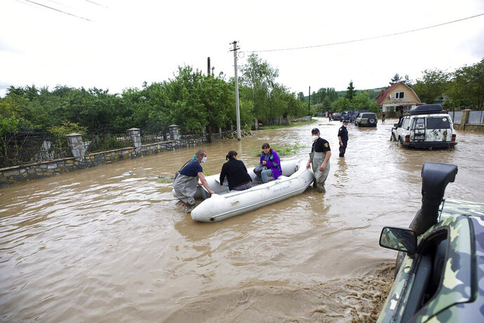 Ukraine's Emergency Situation workers evacuate residents of the flooded village of Lanchyn in the Ivano-Frankivsk region, western Ukraine, Wednesday, June 24, 2020. Some 200 villages in the Carpathian mountains were flooded after heavy rains. (Emergency Situation Ministry via AP)