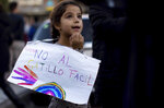 A girl holds a sign that reads in Spanish