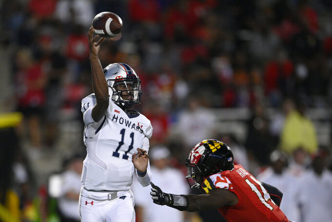 Howard wide receiver Chance Hollingsworth (11) passes under pressure from Maryland defensive back Isaiah Hazel (14) during the second half of an NCAA college football game, Saturday, Sept. 11, 2021, in College Park, Md. (AP Photo/Nick Wass)