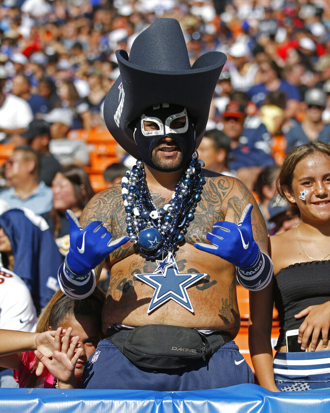 A Dallas Cowboys fan flashes a shaka sign during an NFL preseason football game between the Cowboys and the Los Angeles Rams, Saturday, Aug. 17, 2019, in Honolulu. (AP Photo/Marco Garcia)