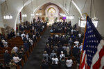 Mourners stand during the funeral Mass for Detective Luis Alvarez, at Immaculate Conception Church, in the Queens borough of New York, Wednesday, July 3, 2019. Alvarez, 53, who died Saturday, June 29, 2019, after a three-year battle with colorectal cancer, fought until his final days for the extension of the Sept. 11 Victim Compensation Fund. (AP Photo/Richard Drew, Pool)