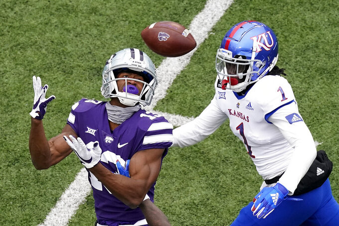 Kansas State wide receiver Chabastin Taylor (13) catches a long pass under pressure from Kansas safety Kenny Logan Jr. (1) during the second half of an NCAA college football game Saturday, Oct. 24, 2020, in Manhattan, Kan. Kansas State won 55-14. (AP Photo/Charlie Riedel)