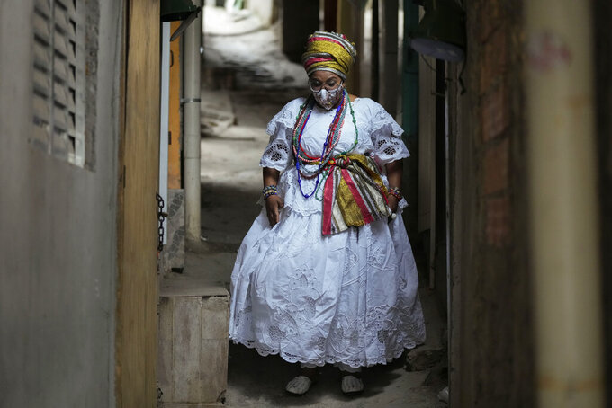 Street food vendor Mila Veloso walks through an alley in the Paraisopolis favela, during the community's centennial celebration, in Sao Paulo, Brazil, Thursday, Sept. 16, 2021. One of the largest favela's in Brazil, home to tens of thousands of residents in the country's largest and wealthiest city, Paraisopolis is grappling with crime and a pandemic that have challenged daily life for many who live there, but organizers say its people have built a vibrant community and are launching a 10-day celebration of its achievements. (AP Photo/Andre Penner)