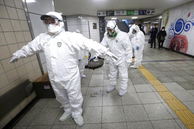 Workers wearing protective gears help clean each other's suits after disinfecting as a precaution against the coronavirus at a subway station in Seoul, South Korea, Friday, Feb. 21, 2020. South Korea on Friday declared a