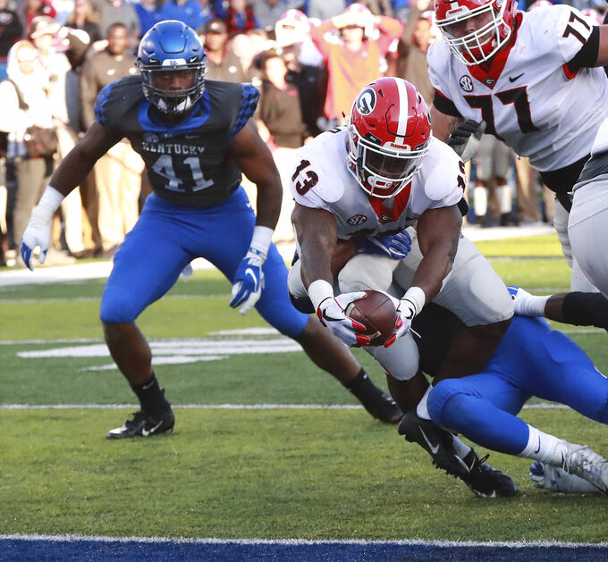 Georgia tailback Elijah Holyfield stretches for the goal line for a touchdown  during the third quarter in a NCAA college football game on Saturday, Nov. 3, 2018, in Lexington, Ky. (Curtis Compton/Atlanta Journal-Constitution via AP)