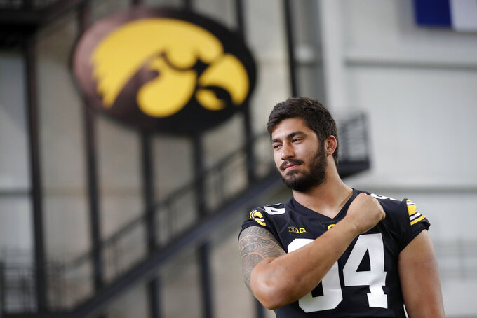 FILE - In this Aug. 10, 2018, file photo, Iowa defensive end A.J. Epenesa poses for photographers during an NCAA college football media day, in Iowa City, Iowa. Iowa junior Epenesa knows that he has a strong shot at being picked in the first round of the 2020 NFL Draft should he choose to go pro next spring. He's just choosing not to think about it until then. Epenesa, a 6-foot-6, 280-pound defensive end who led the Big Ten with 10.5 sacks a year ago despite coming off the bench, is poised for a monster season in 2019. (AP Photo/Charlie Neibergall, File)