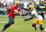 Green Bay Packers quarterback Aaron Rodgers (12) hands the ball off to running back Dexter Williams (22) during NFL team practice, Tuesday, June 4, 2019 in Ashwaubenon, Wis. (Chris Kohley/The Post-Crescent via AP)