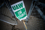 FILE - In this Sept. 16, 2019, file photo, a United Auto Workers strike sign rests between the chains of a locked gate entrance outside of Flint Engine Operations in Flint, Mich. General Motors CEO Mary Barra joined negotiators at the bargaining table Tuesday, Oct. 15, an indication that a deal may be near to end a monthlong strike by members of the United Auto Workers union that has paralyzed the company's factories. (Jake May/The Flint Journal via AP, File)