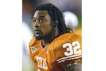 FILE -  In this Nov. 6, 2004 file photo Texas running back Cedric Benson is shown in the bench area during the fourth quarter of his team's 56-35 victory over Oklahoma State in Austin, Texas. Benson, one of the most prolific rushers in NCAA and University of Texas history, has died in a motorcycle accident in Texas, Saturday, Aug. 17, 2019. He was 36. (AP Photo/Harry Cabluck, file)