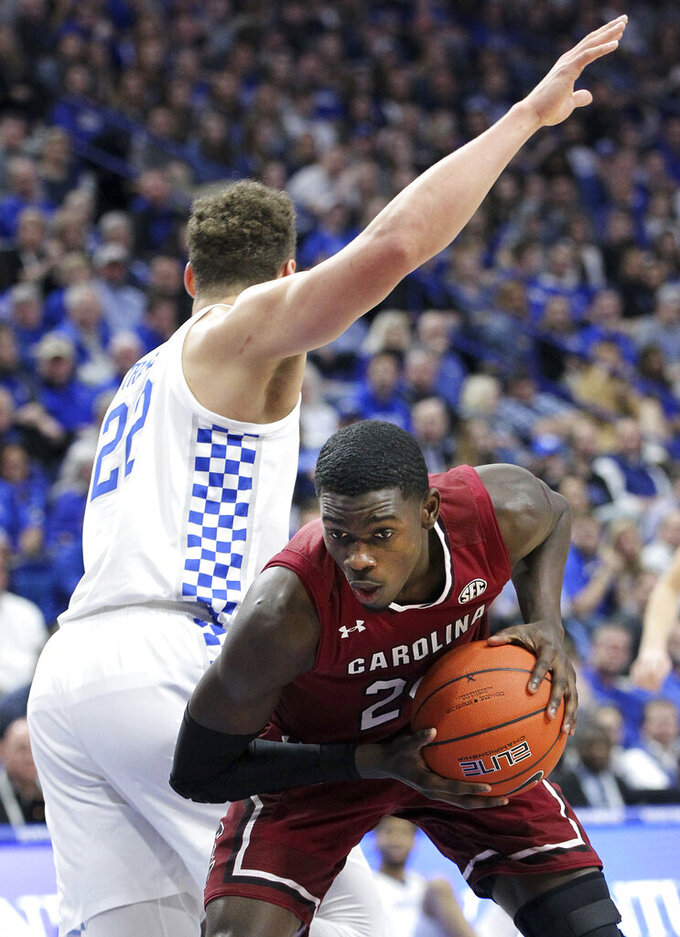 South Carolina's Keyshawn Bryant, right, pulls down a rebound below Kentucky's Reid Travis, left, during the first half of an NCAA college basketball game in Lexington, Ky., Tuesday, Feb. 5, 2019. (AP Photo/James Crisp)