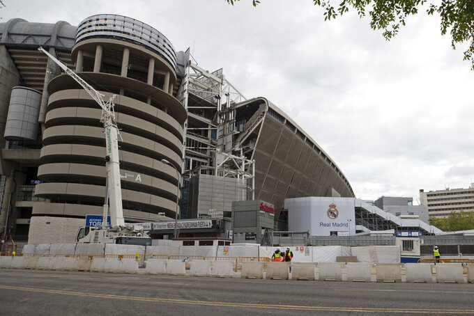 Constuction workers stand by Real Madrid's Santiago Bernabeu stadium in Madrid, Spain, Thursday, April 16, 2020. The Covid-19 coronavirus pandemic has affected more than games and player salaries for Real Madrid and Barcelona. It has also taken a toll on their stadium renovation plans. Both Spanish soccer clubs are working on hefty renovation projects for their famed venues.(AP Photo/Paul White)