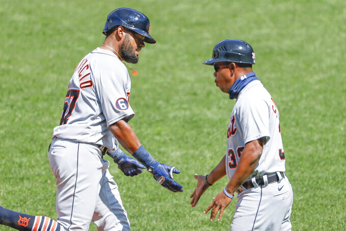 Detroit Tigers' Jorge Bonifacio, left, gets congratulations from third base coach Ramon Santiago after hitting a two-run home run off Cleveland Indians starting pitcher Carlos Carrasco during the fourth inning of a baseball game, Sunday, Aug. 23, 2020, in Cleveland. (AP Photo/Ron Schwane)