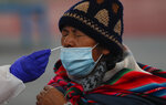 A health worker collects a sample from a resident during testing for the new coronavirus at a sports facility in La Paz, Bolivia, Friday, Jan. 8, 2021. (AP Photo/Juan Karita)