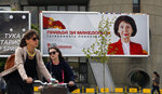 People cycle past a campaign poster of Gordana Siljanovska Davkova, a candidate for the opposition conservative VMRO-DPMNE party that reads in Macedonian