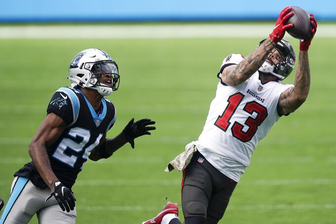 Tampa Bay Buccaneers wide receiver Mike Evans (13) makes the catch against Carolina Panthers cornerback Rasul Douglas (24) during the first half of an NFL football game, Sunday, Nov. 15, 2020, in Charlotte , N.C. (AP Photo/Gerry Broome)