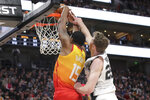 Utah Jazz forward Derrick Favors (15) is fouled by San Antonio Spurs center Jakob Poeltl (25) while trying to dunk during the second quarter of an NBA basketball game, Saturday, Feb. 9, 2019, in Salt Lake City. (AP Photo/Chris Nicoll)