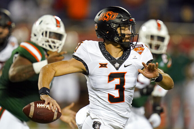 Oklahoma State quarterback Spencer Sanders (3) looks for a receiver as he is pressured by the Miami defense during the first half of the Cheez-it Bowl NCAA college football game, Tuesday, Dec. 29, 2020, in Orlando, Fla. (AP Photo/John Raoux)