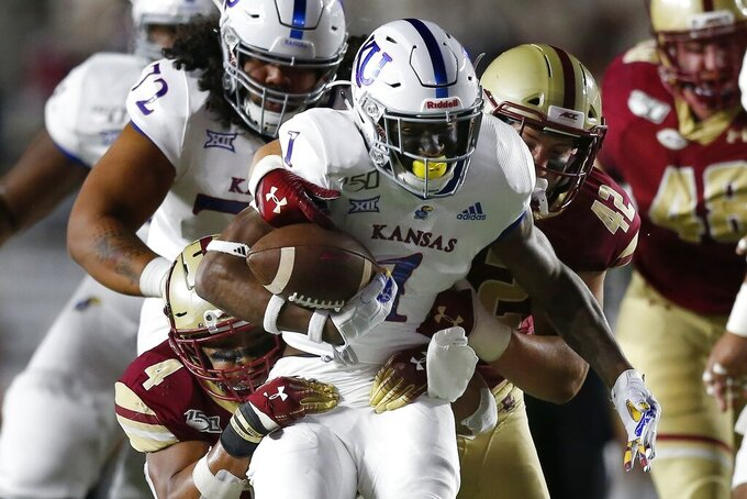 Boston College wide receiver Zay Flowers (4) and linebacker Vinny DePalma (42) tackle Kansas running back Pooka Williams Jr. (1) during the first half of an NCAA college football game in Boston, Friday, Sept. 13, 2019. (AP Photo/Michael Dwyer)