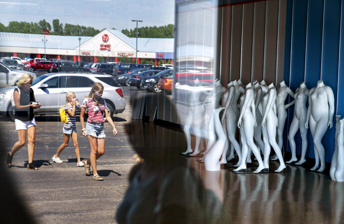 Mannequins stand in an empty store as shoppers visit outlet shops in Oshkosh, Wis., part of the greater Appleton area, Aug. 20, 2020. Storefronts after the pandemic have been emptied at the Oshkosh Outlets, including the nearby Brooks Brothers, the haberdashery for generations of presidents, that filed for bankruptcy this year. (AP Photo/David Goldman)