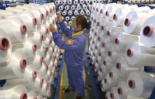 An employee works in a chemical fiber plant in Nantong in eastern China's Jiangsu Province, Friday, Jan. 17, 2020. China's economic growth sank to a new multi-decade low in 2019 as Beijing fought a tariff war with Washington, but forecasters said a U.S.-Chinese trade truce might help to revive consumer and business activity. (Chinatopix via AP)