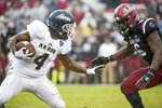 Akron running back Deltron Sands (4) runs with the ball against South Carolina linebacker T.J. Brunson (6) during the first half of an NCAA college football game Saturday, Dec. 1, 2018, in Columbia, S.C. South Carolina defeated Akron 28-3. (AP Photo/Sean Rayford)
